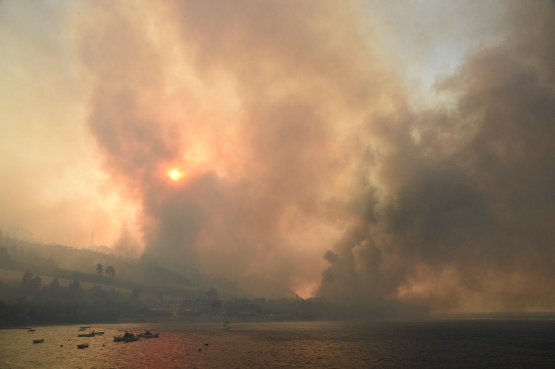 Griechenland: Dichter Rauch steigt von einem Waldbrand in der Nähe des Dorfes Lampiri, westlich von Patras auf. Das an einem Berghang ausgebrochene Feuer hat sich in gefährliche Nähe zu den Küstenstädten ausgebreitet, woraufhin die Feuerwehr ein Boot für die mögliche Evakuierung der Bewohner zur Verfügung gestellt hat.