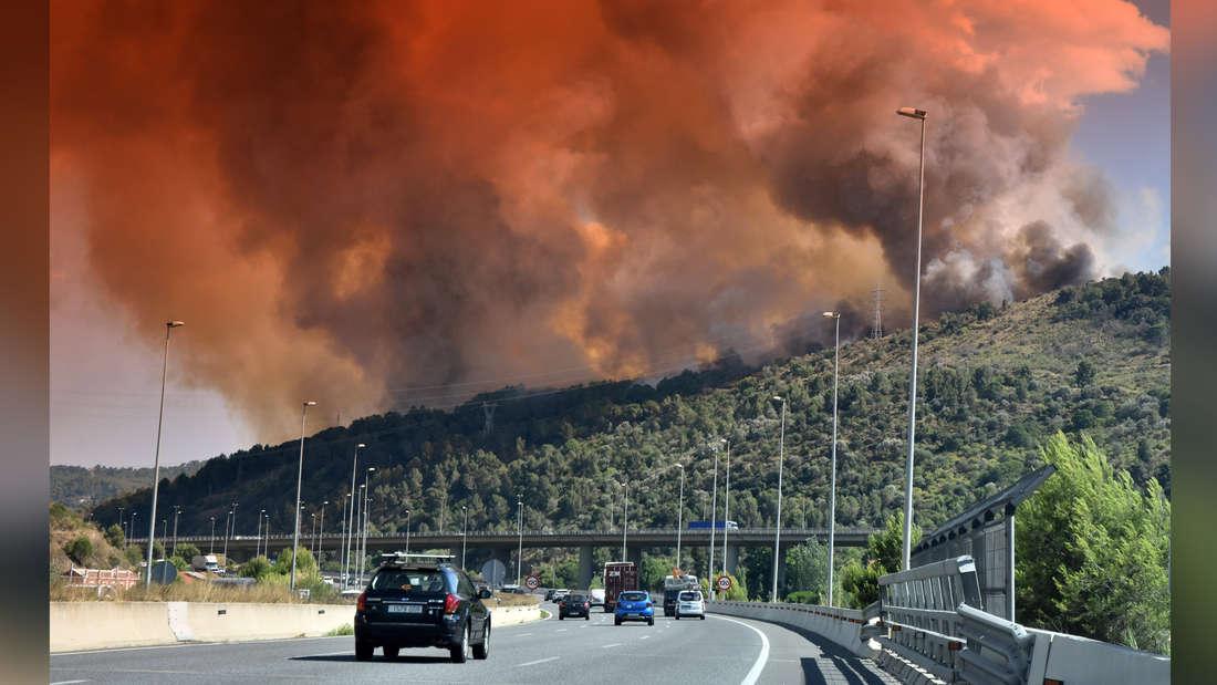 Eine Rauch- und Feuerwolke in Castellvi de Rosanes, die während des Feuers über der Autobahn A-2 in Martorell gesehen wurde. Ein Waldbrand verbrennt mehr als 150 Hektar Waldmasse zwischen den Städten von Castellvi de Rosanes und Martorell.