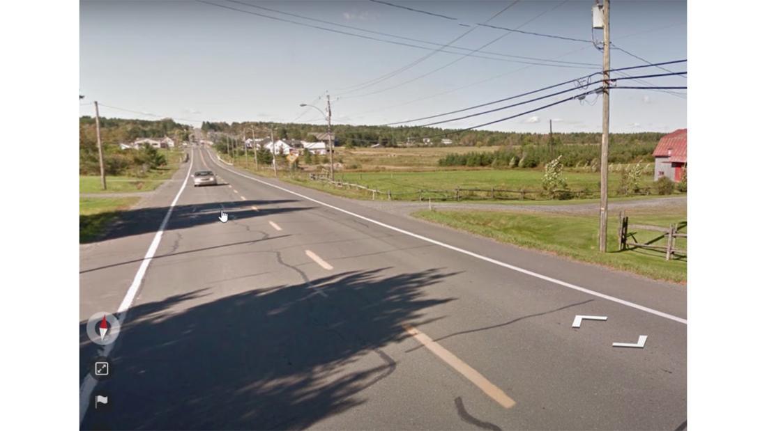 Ein Bild von Google Street View, das eine Straße, viel Grün, Telefonmasten und ein Auto zeigt.