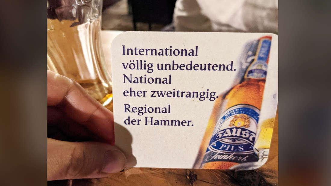 """Ein Untersetzer von FAUST Pils, auf dem steht: """"International völlig unbedeutend. National eher zweitrangig. Regional der Hammer."""""""