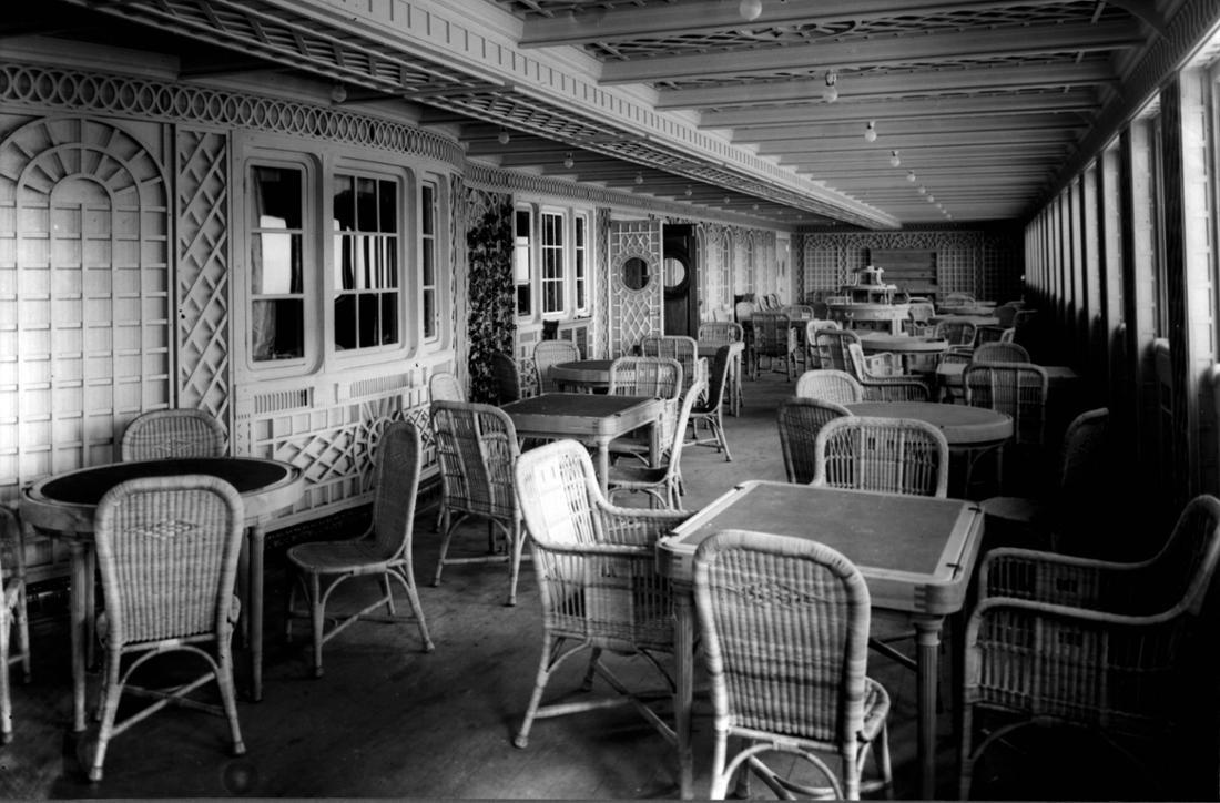 Schwarz-Weiß-Aufnahme  einer groß angelegten Veranda mit mehreren Tischen, um die herum jeweils vier Korbstühle platziert sind. Die Wände und Fenster sind mit Holzreliefs verziert.