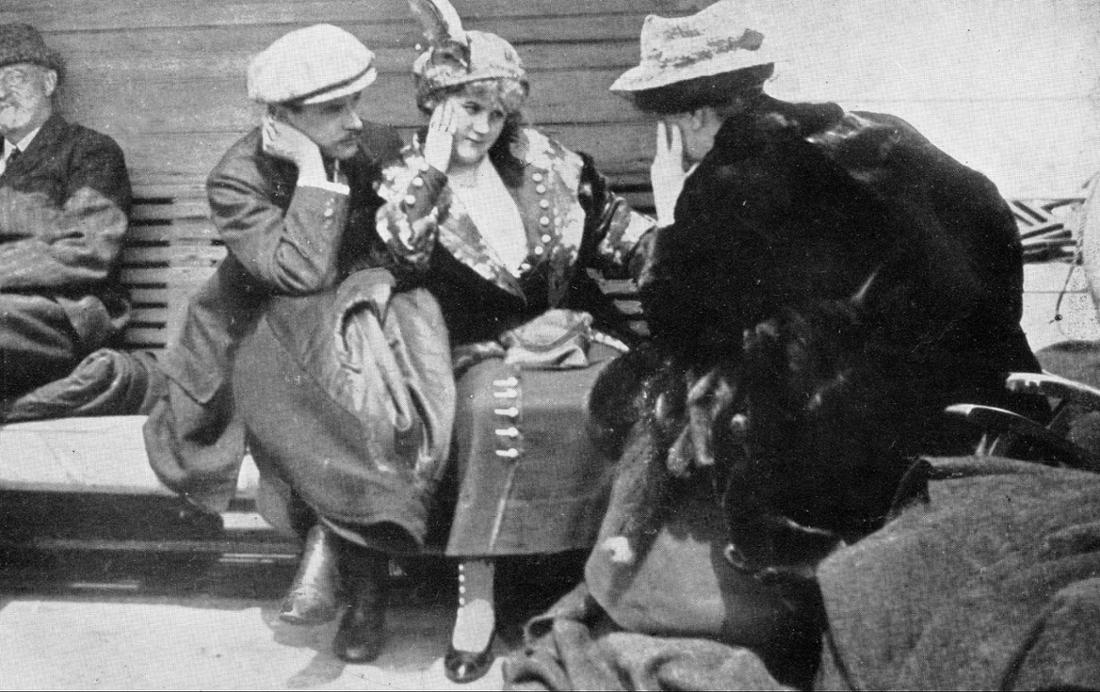 Schwarz-Aufnahme von einem Mann und einer Frau, die auf einer Bank sitzen und eine Frau ansehen, die mit dem Rücken zur Kamera sitzt