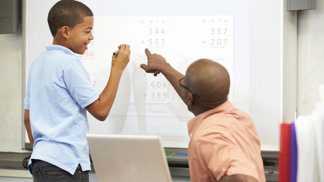 Ein Mann, der einem Kind an einem Smartboard eine Rechenaufgabe zeigt.