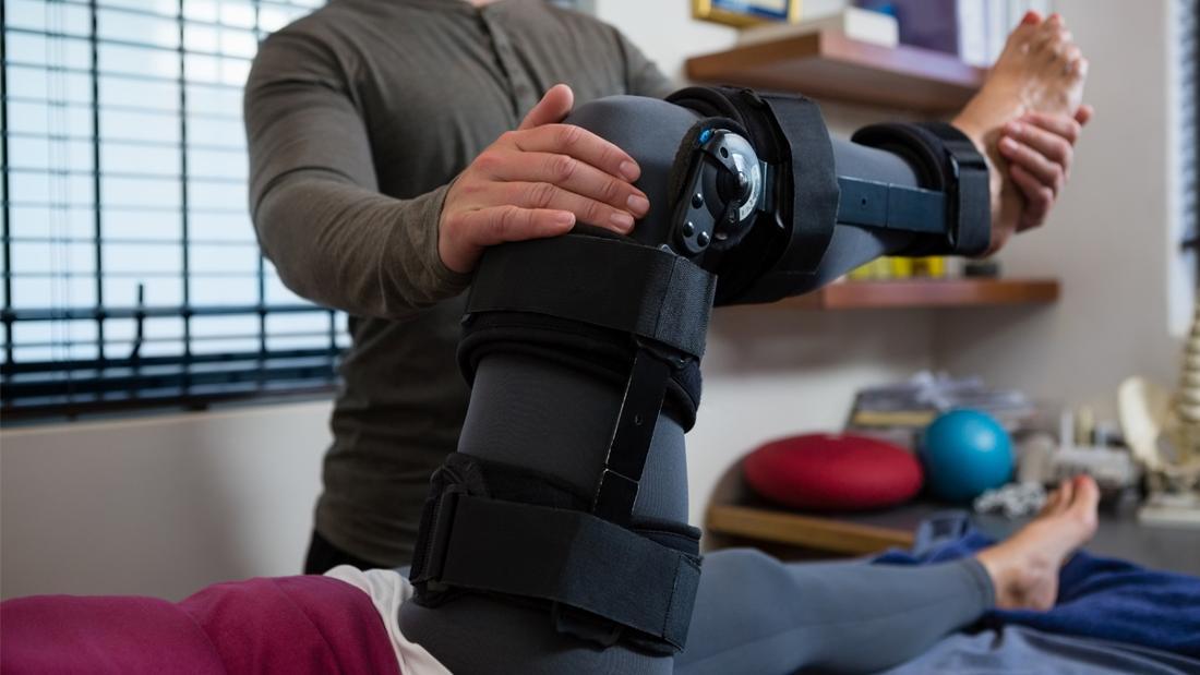 Eine Person, der einer Frau mit Beinschiene hilft, ihr Bein durchzudrücken.