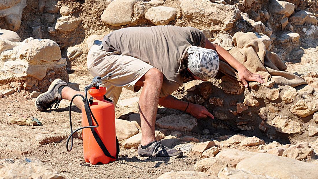 Ein Archäologe, der Gestein untersucht.