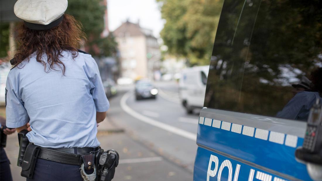 Eine Polizistin, die neben ihrem Polizeiauto steht.
