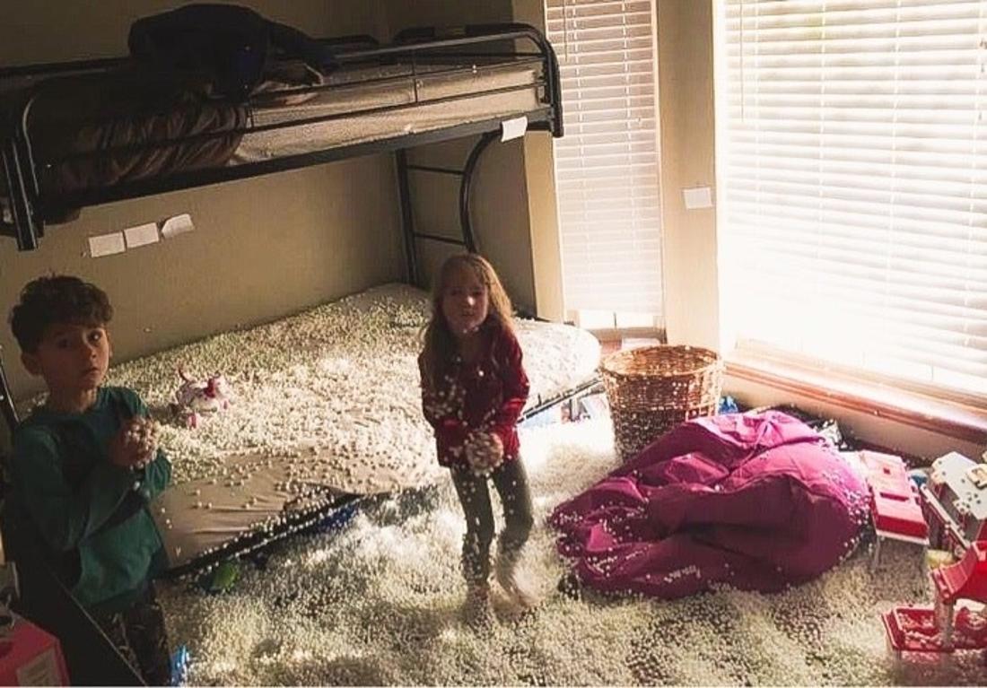 Zwei Kinder, die in einem großen Haufen weißer Kügelchen spielen.