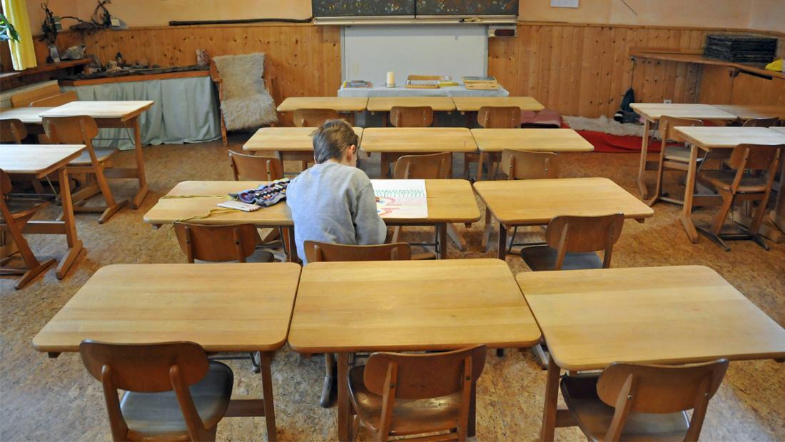 Ein Junge, der alleine in einem Klassenzimmer sitzt.