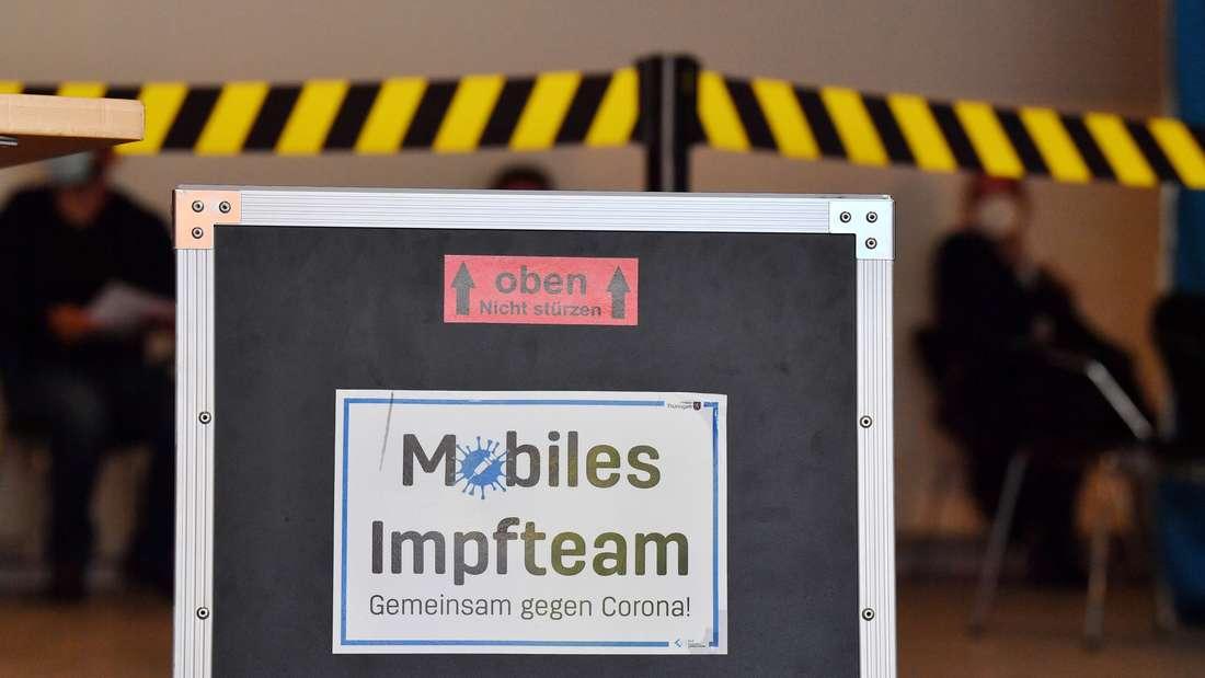 """""""Mobiles Impfteam"""" steht auf einer Kiste während einer Impfaktion"""