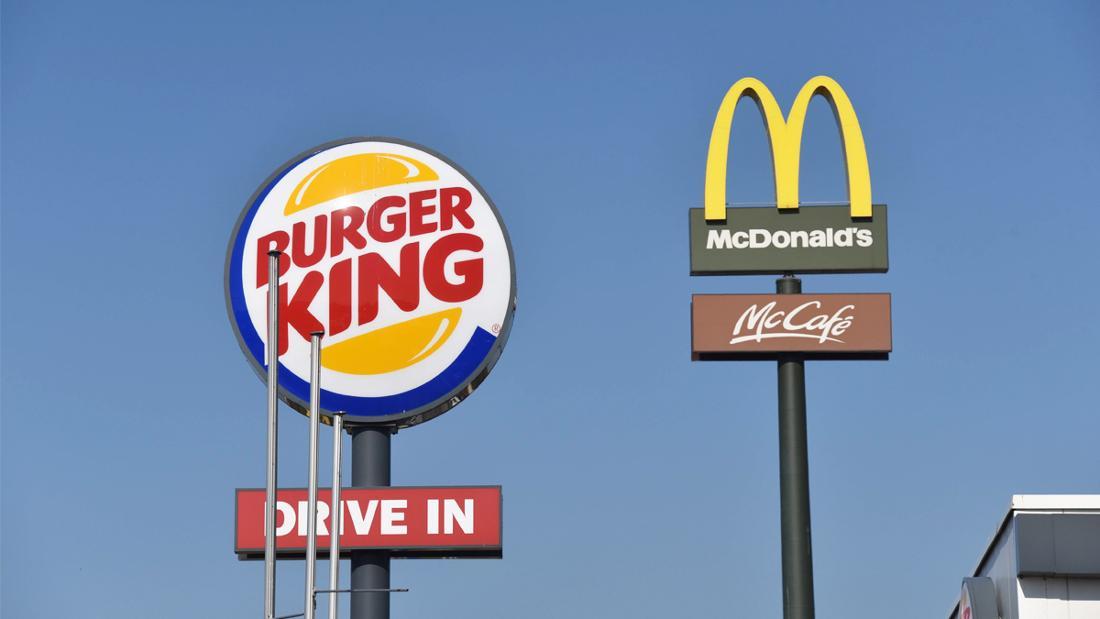Vier Schilder: Eines von Burger King und dem Drive In und eines von McDonald's und dem McCafé.