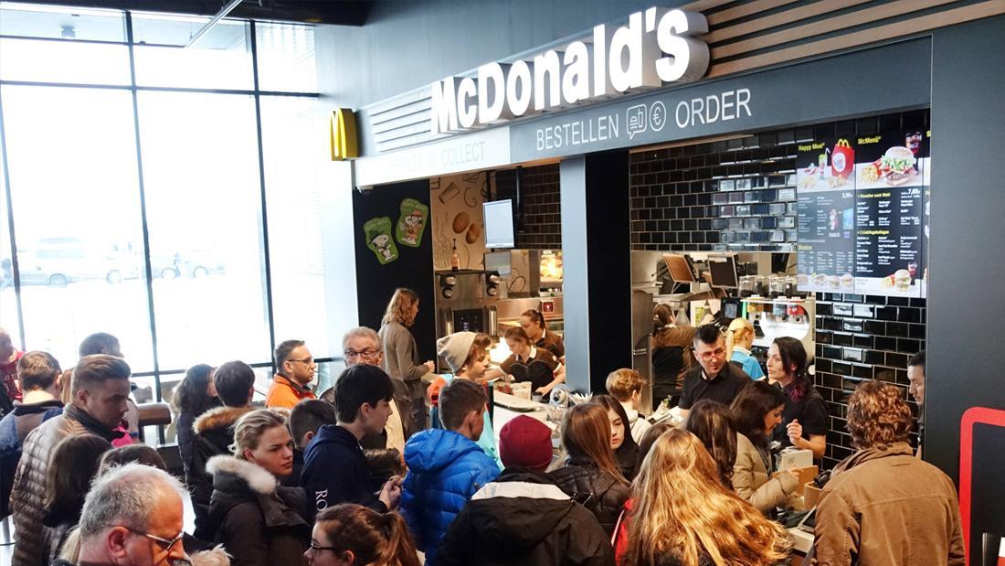 Viele Kund*innen, die vor der Bestelltheke in einem McDonald's-Restaurant stehen.