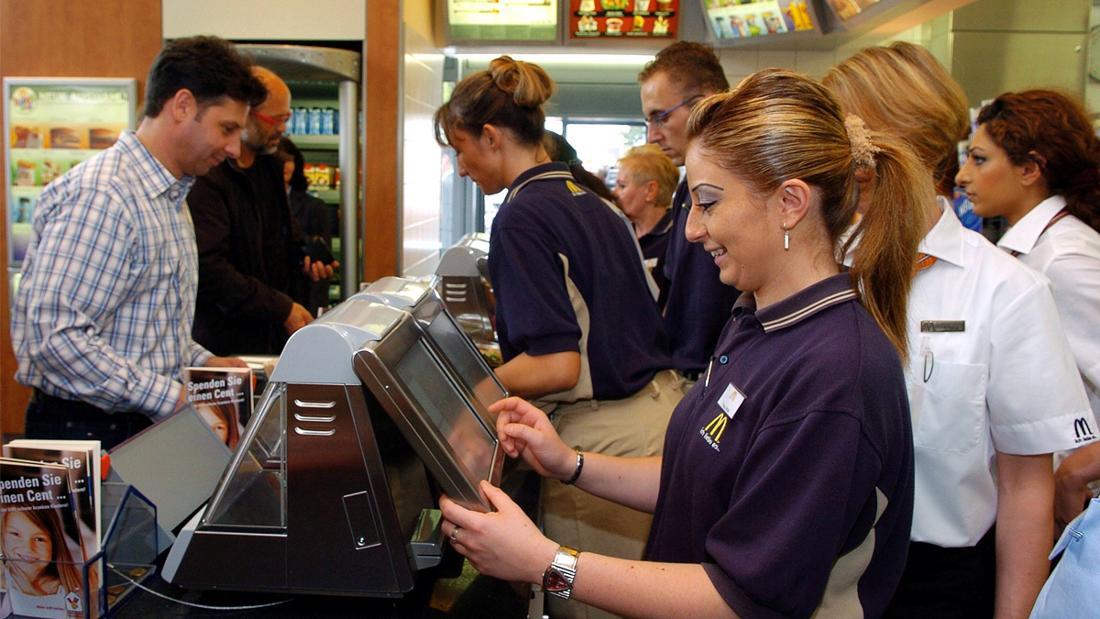 Eine McDonald's-Mitarbeiterin, die Kund*innen in einem McDonald's-Restaurant bedient.