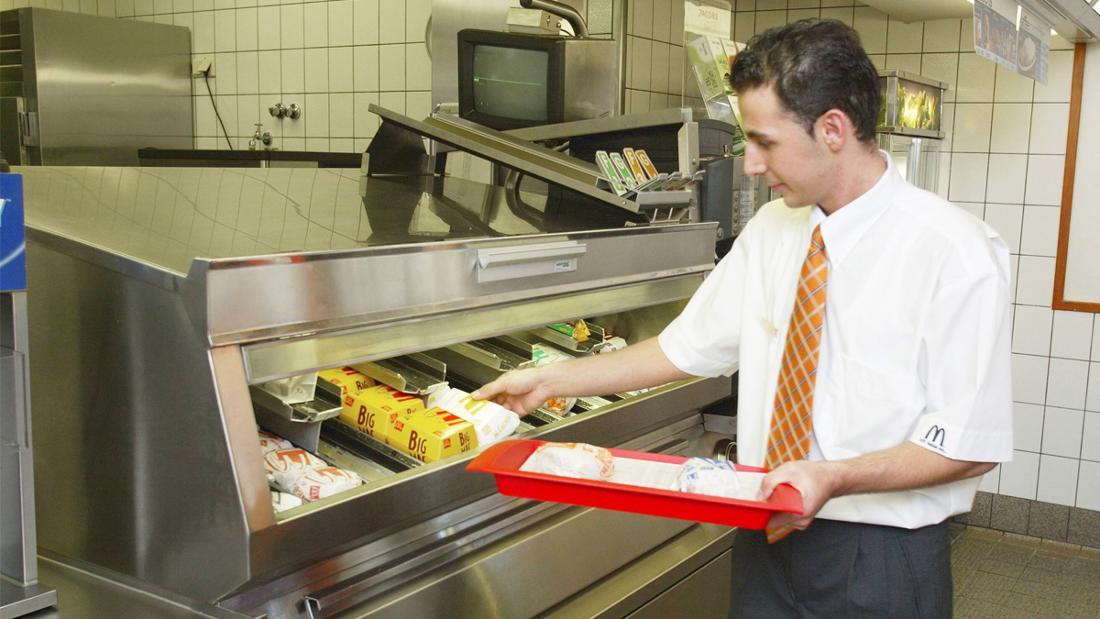 Ein Mann in einer McDonald's-Uniform, der gerade Burger auf ein Tablett legt.