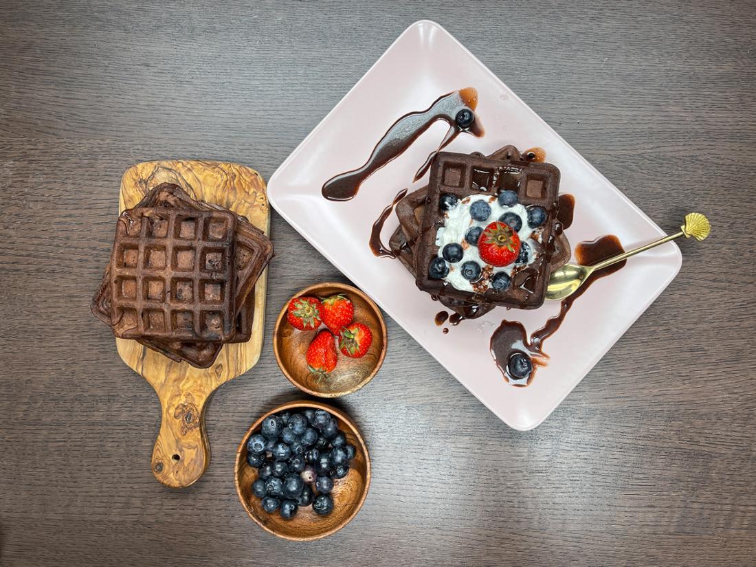Ein Holzbrett mit Schokowaffeln, Erdbeeren und Blaubeeren in Schüsseln und dekorierte Schokowaffeln auf einem viereckigen Teller.