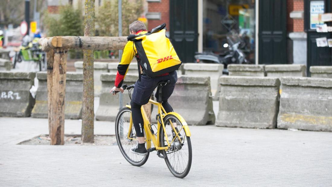 DHL-Mitarbeiter fährt auf einem Fahrrad.