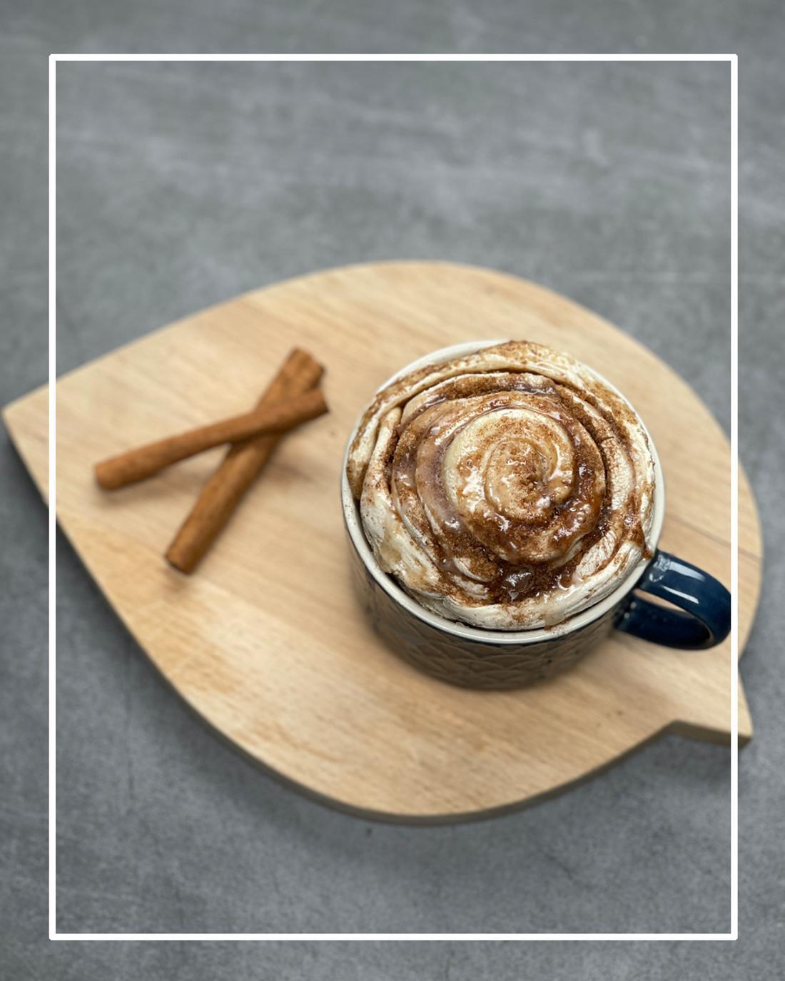 Eine Tasse, die auf einem Holzbrett steht und in der eine Zimtschnecke liegt.