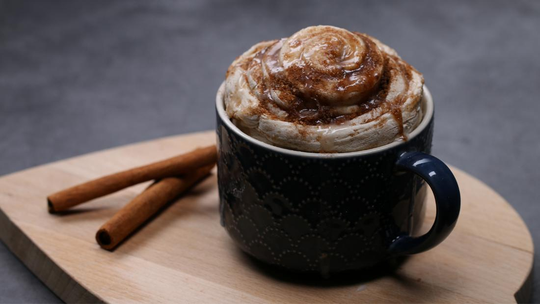 Eine Tasse, die auf einem Holzbrett steht und in der eine Zimtschnecke steckt. Neben ihr liegen zwei Zimtstangen.