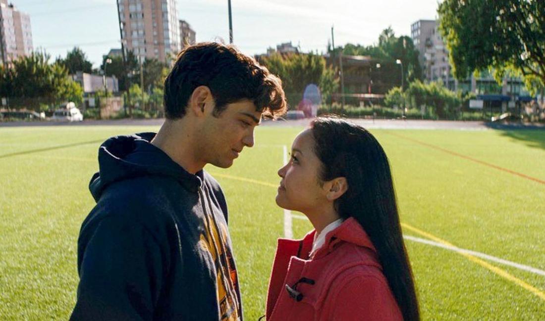 Noah Centineo und Lana Condor stehen auf einem Football-Feld und sehen einander tief in die Augen.