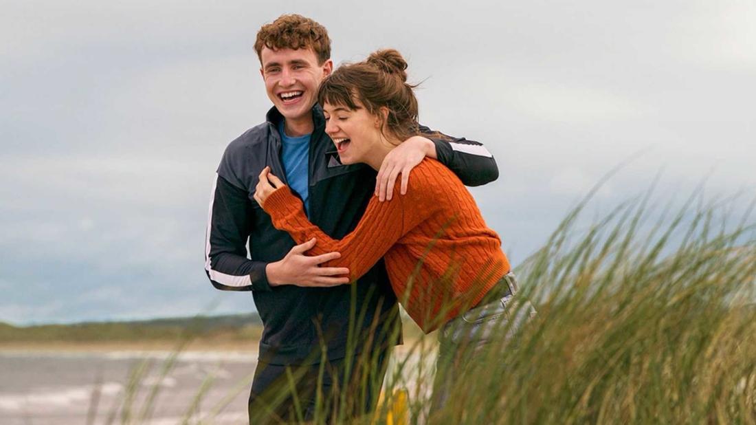 Paul Mescal und Daisy Edgar-Jones umarmen einander lachend am Strand