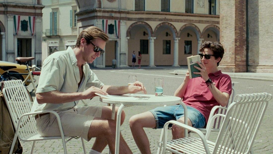 Armie Hammer und Timothé Chalamet sitzen an einem Café-Tisch in der Sonne.