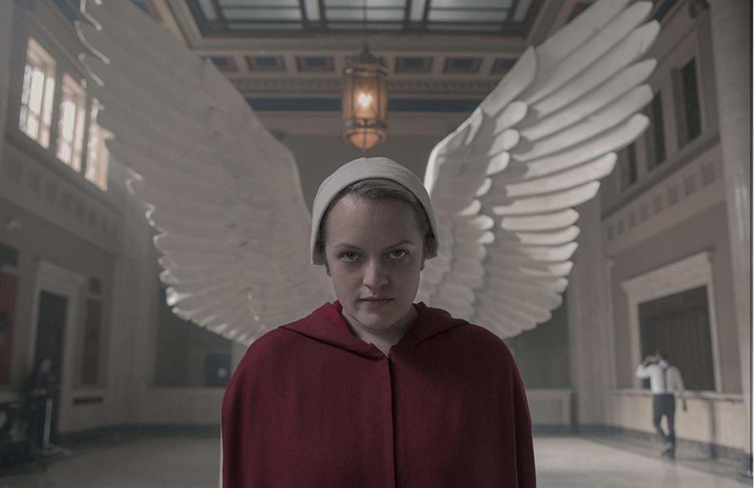 Elizabeth Moss steht in ihrem roten Umhang und der weißen Kappe vor zwei Engelsflügeln, die einer Statue gehören.