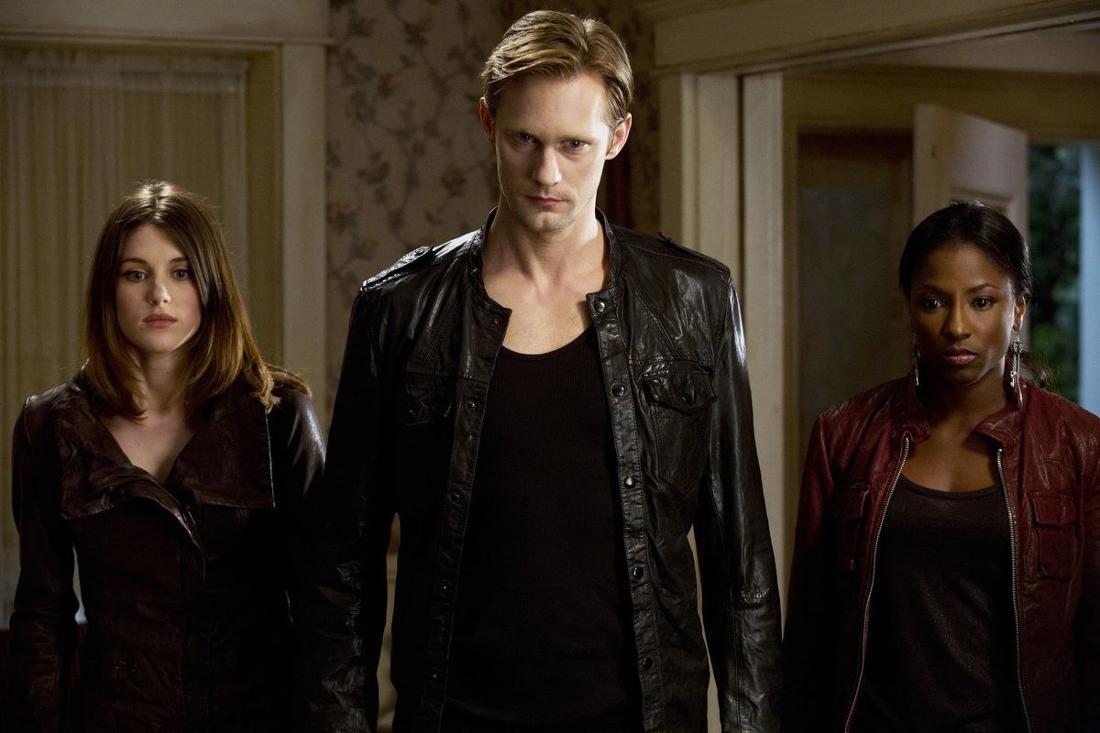 Lucy Griffiths, Alexander Skarsgård und Rutina Weasley stehen in einem Wohnzimmer.