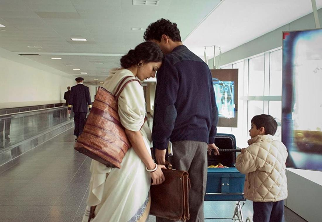 Eine Frau lehnt die Stirn an die Schulter eines Mannes, während ein Kind zu ihnen aufsieht.
