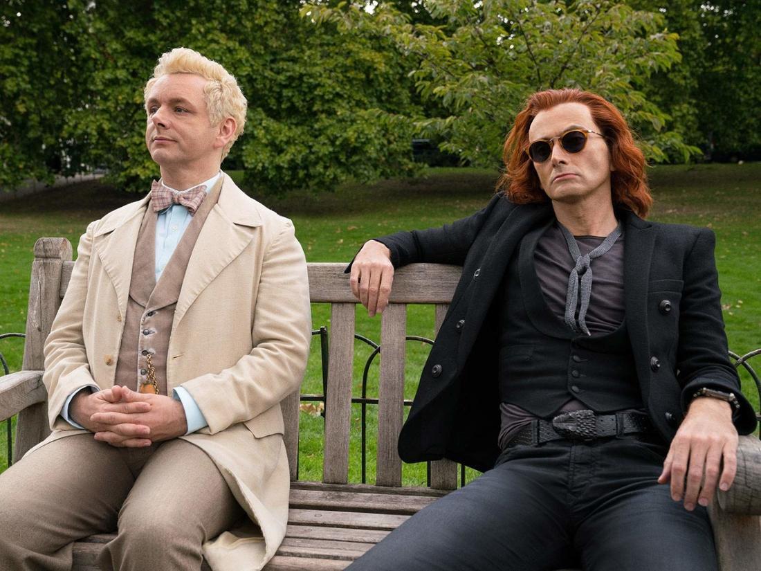 Michael Sheen und David Tennant sitzen nebeneinander auf einer Parkbank