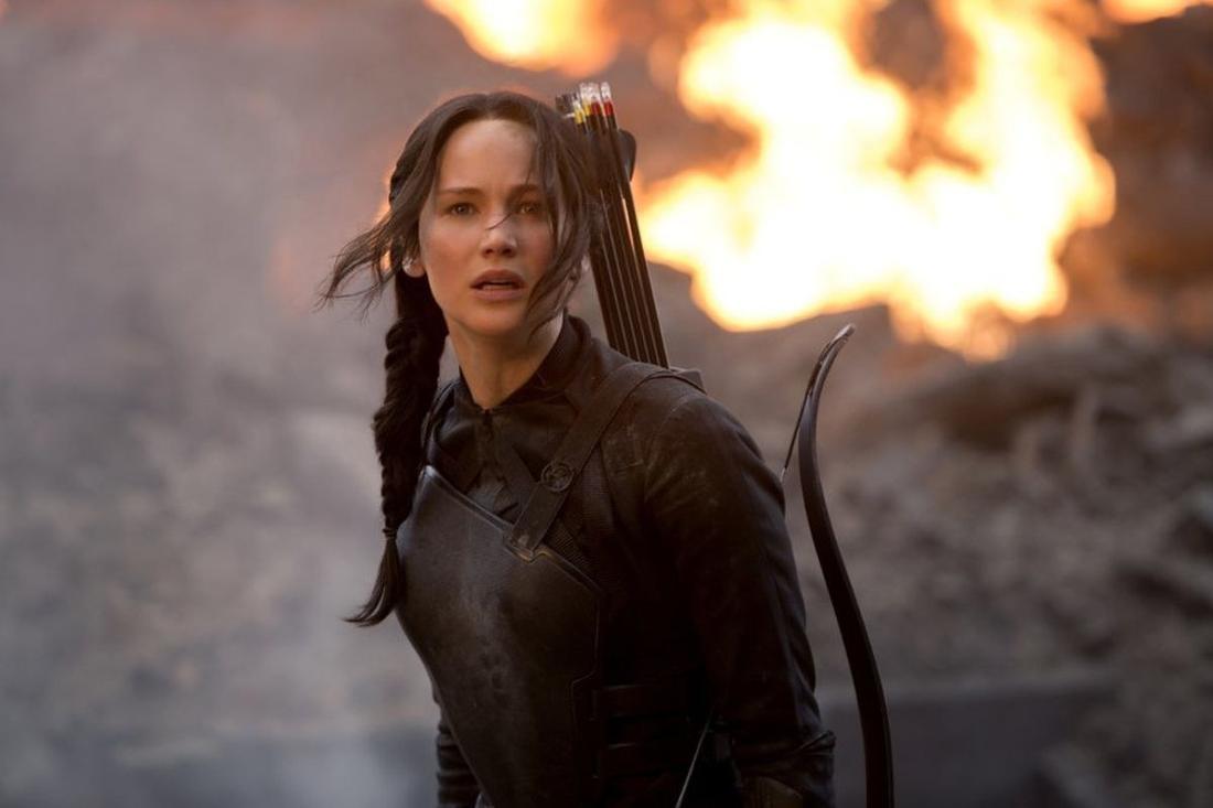 Jennifer Lawrence steht vor einem Feuer und schaut in die Ferne.