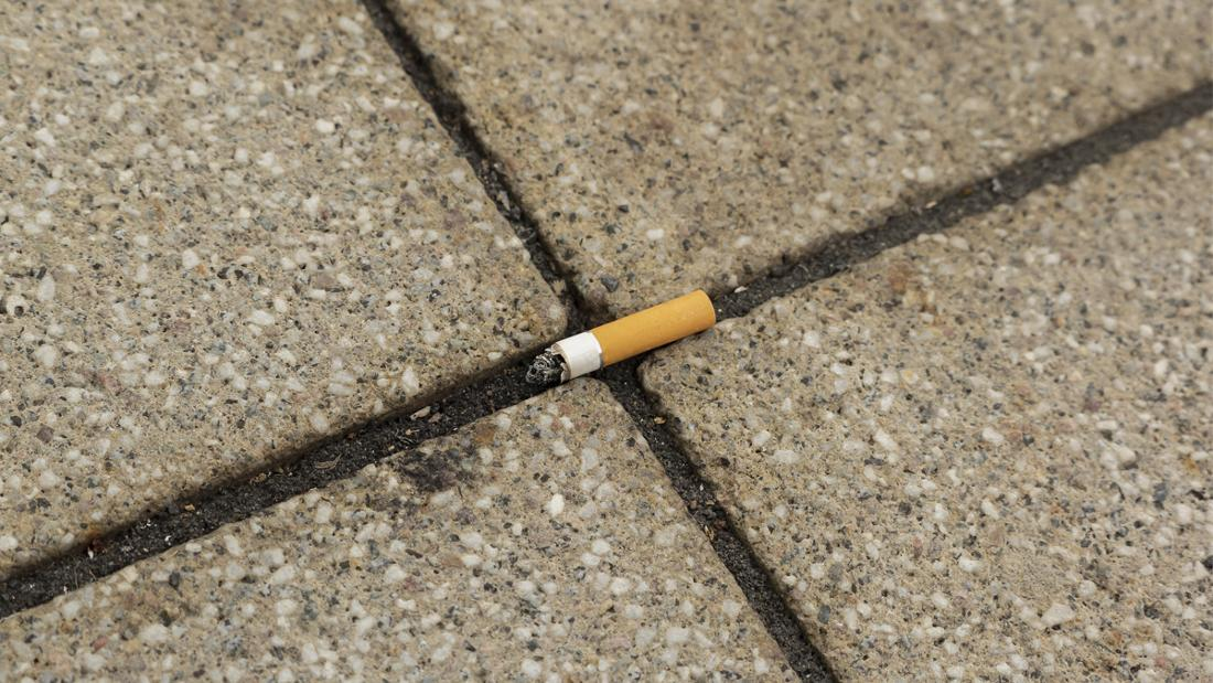 Eine Zigarette, die ausgetreten auf dem Boden liegt.