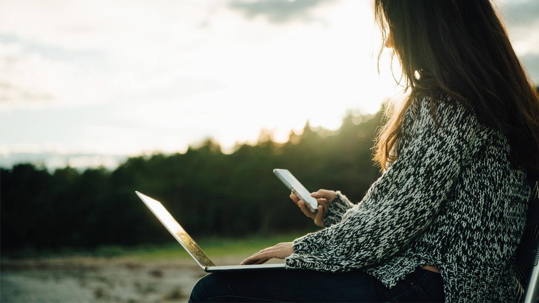 Eine Frau, die mit ihrem Laptop bei Sonnenuntergang am Strand sitzt und auf ihr Handy guckt.