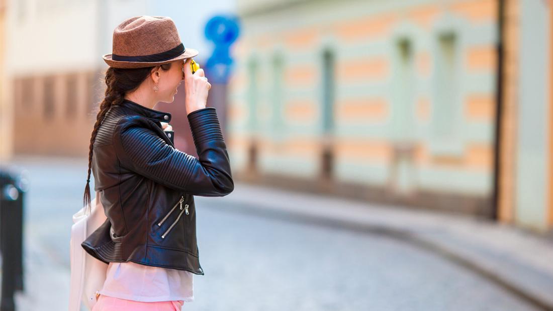 Eine Frau, die auf einer Straße ein Foto macht.