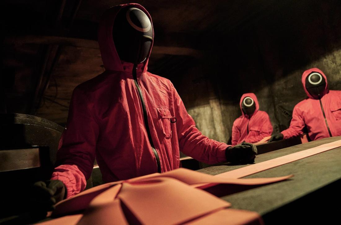 Eine Gruppe Männer in roten Anzügen stehen in einer dunklen Kammer um einen Tisch herum.