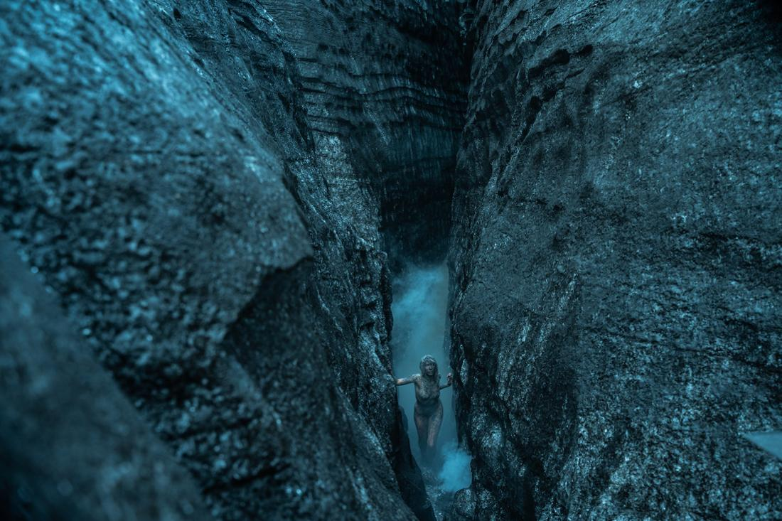 Eine nackte Frau steigt aus einer Felsspalte