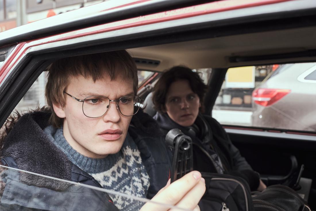 Ein Mann sitzt im Auto und schaut verdutzt auf den Fenstergriff in seiner Hand