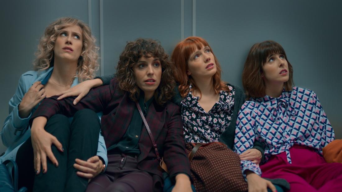 Vier Frauen sitzen auf dem Boden eines Fahrstuhls