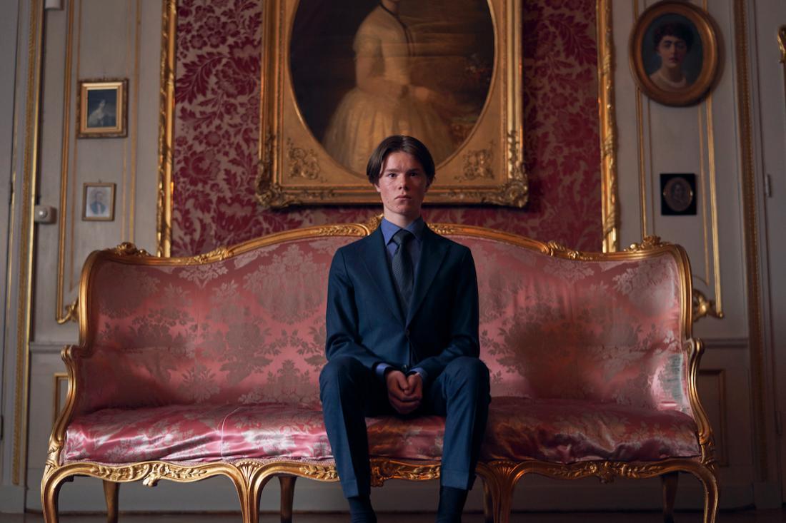 Ein junger Mann sitzt vor einem Familienporträt auf einem opulenten Sofa