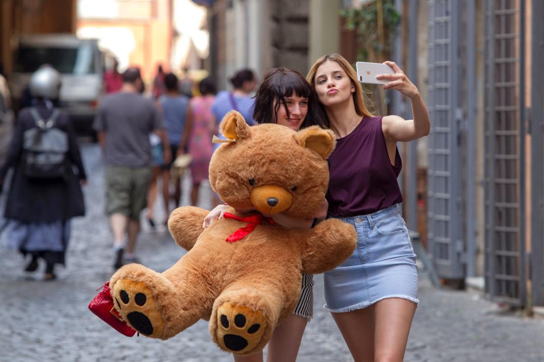 Zwei Mädchen laufen mit einem großen Teddy die Straße entlang und machen ein Selfie