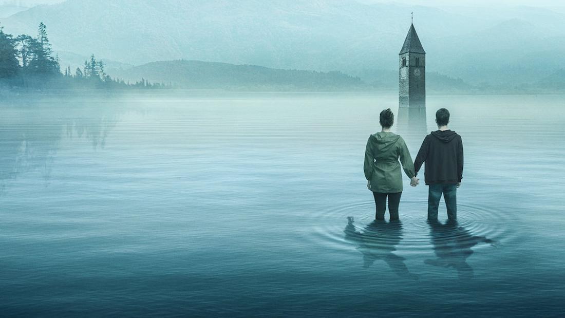 Zwei Menschen stehen bis zu den Knien im Wasser eines Sees, aus dem ein Kirchturm ragt.