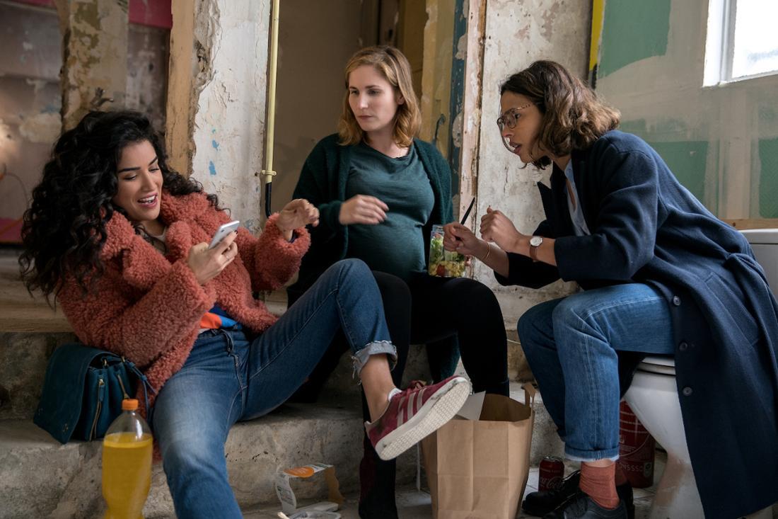 Drei Frauen sitzen zusammen und schauen aufgeregt auf das Handy der einen.