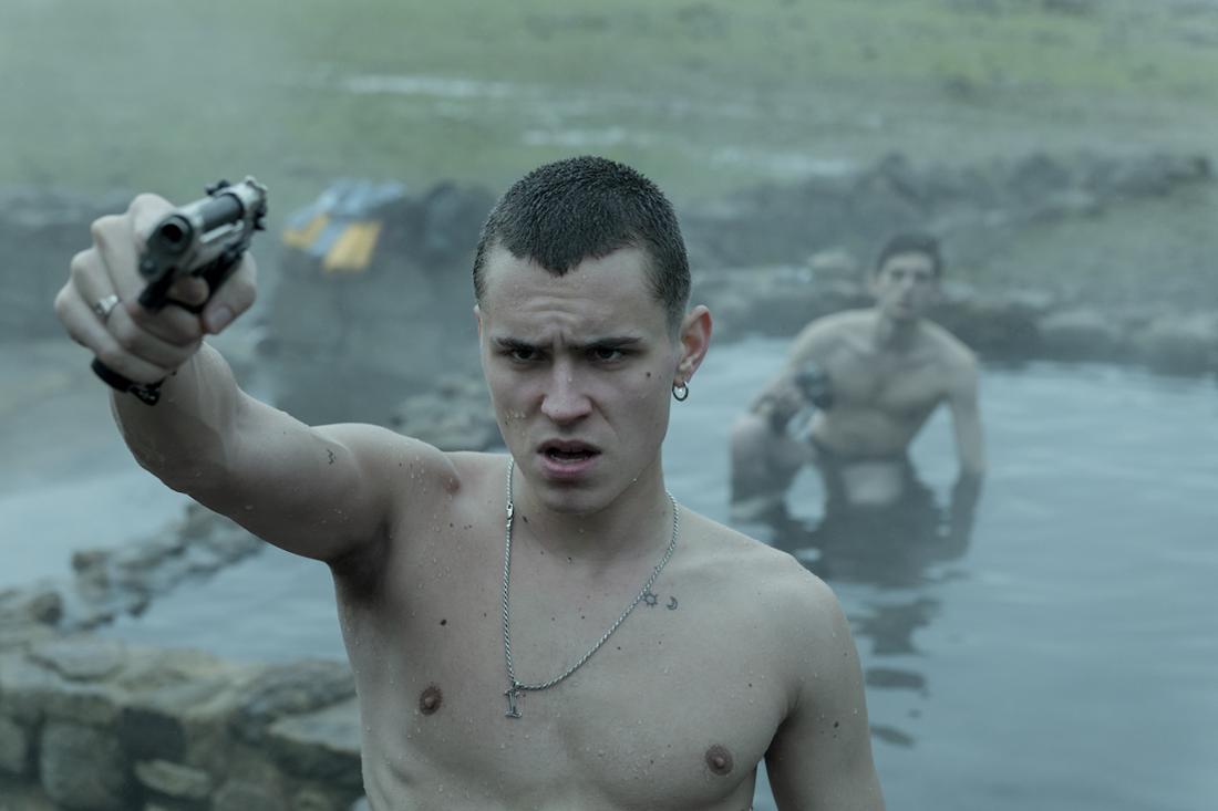 Ein Mann mit freiem Oberkörper zielt mit der Waffe auf jemanden