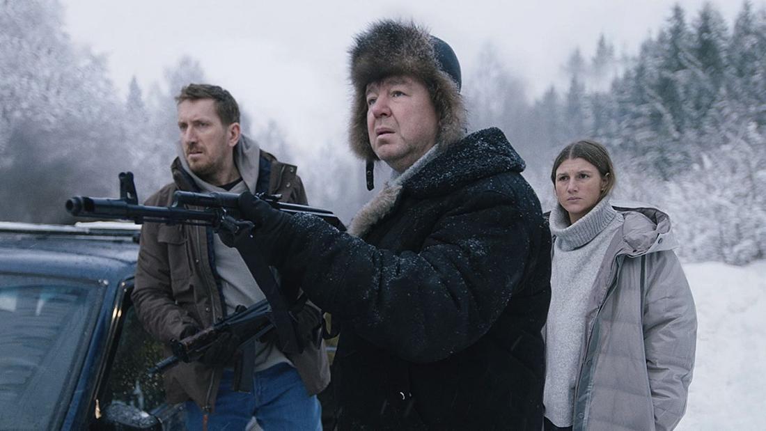 Drei Leute stehen auf einer zugeschneiten Straße, zwei von ihnen halten Gewehre.