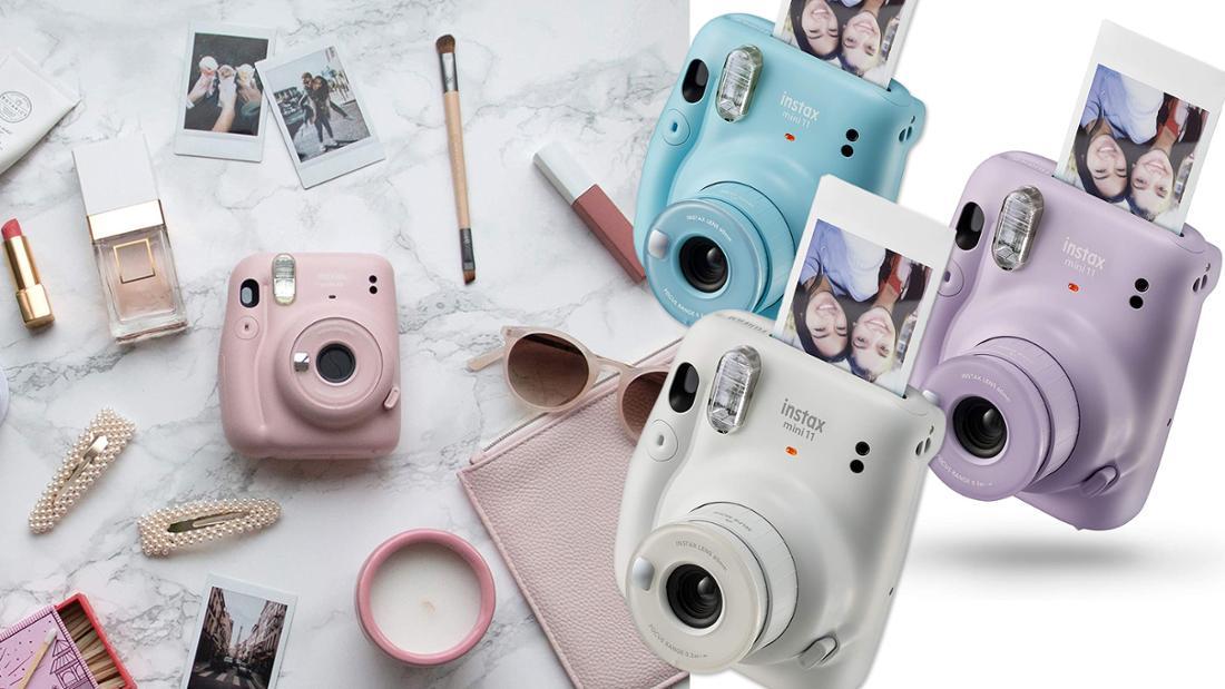 Etwa Handgroße Sofortbildkamera mit ausfahrbarem Objektiv, Blitz und Öffnung für Fotos. Abgebildet sind die erhältlichen Farben rosa, violet, hellblau und Ice White.