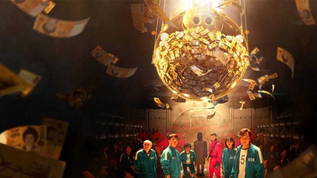 """Die Teilnehmer*innen, die in der Netflix-Serie """"Squid Game"""" in gefährlichen Spielen um viel Geld spielen: Gi-hun, Sang-woo, Il-nam, Sae-Byeok, Deok-su, Mi-nyeo, der Front Man und der Polizist Jun-ho. Sie stehen alle unter einem Sparschwein mit viel Geld. Um sie herum stehen Wächter*innen und andere Spieler*innen."""