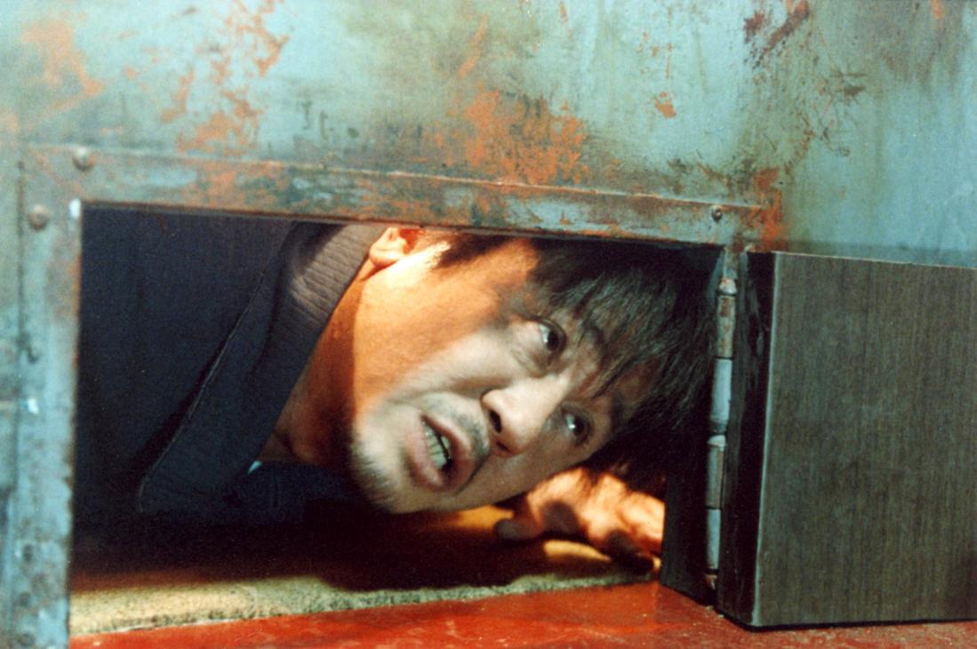 OLDBOY: Ein Mann streckt den Kopf durch eine kleine Öffnung am Fuß einer Tür.