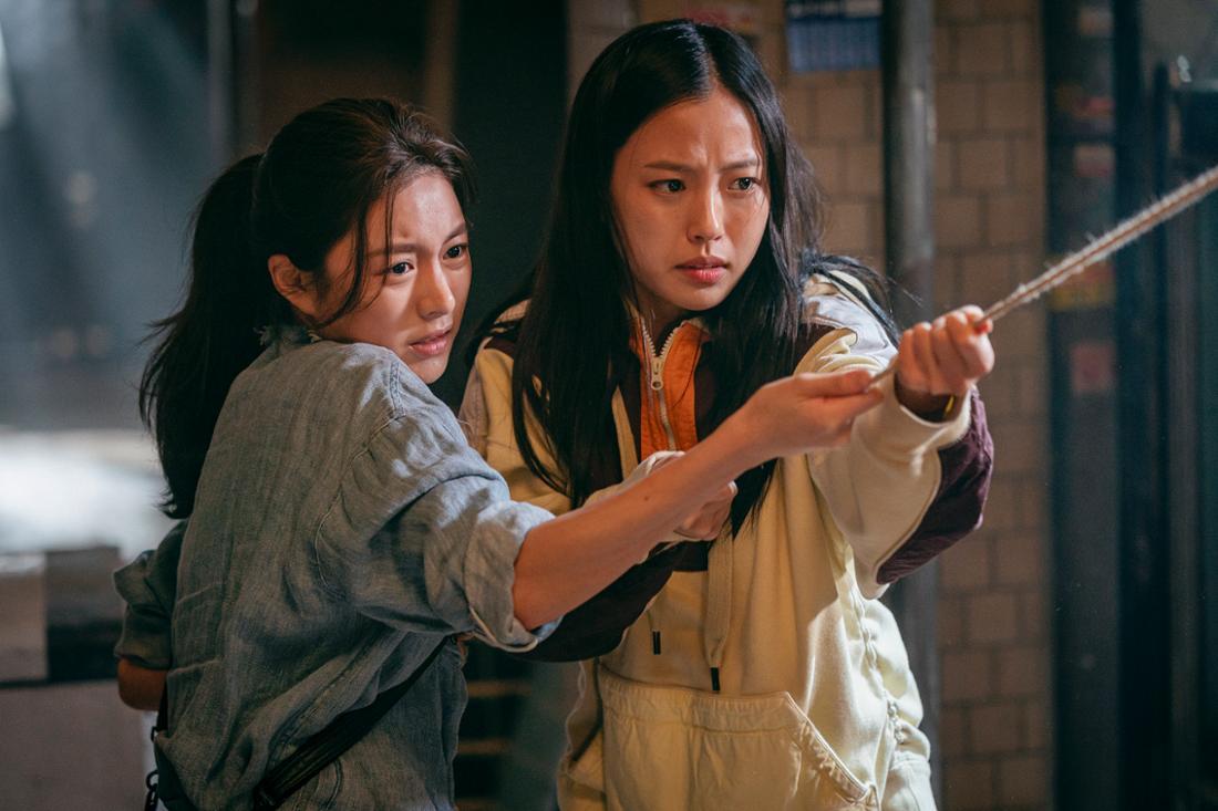 Sweet Home: Zwei junge Frauen halten gemeinsam angestrengt ein Seil fest.