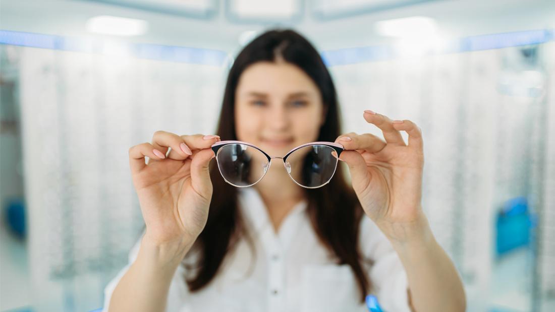 Eine Frau, die eine Brille hält. Außer der Brille und ihrer Hände ist alles im Bild verschwommen.