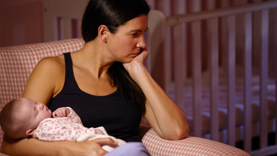 Eine Frau, die ihr Baby im Arm hält und traurig aussieht.